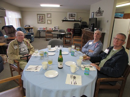 Picture of three veterans sitting around a table dining and drinking