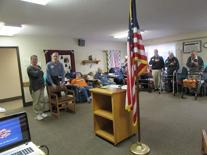 Picture of veterans in a room standing for the national anthem