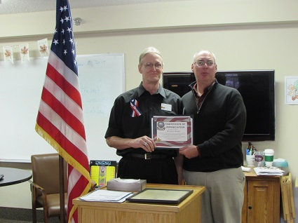 Picture of Paul Welch presenting a United States Marine Corps Certificate of Appreciation to Mitchell Nelson